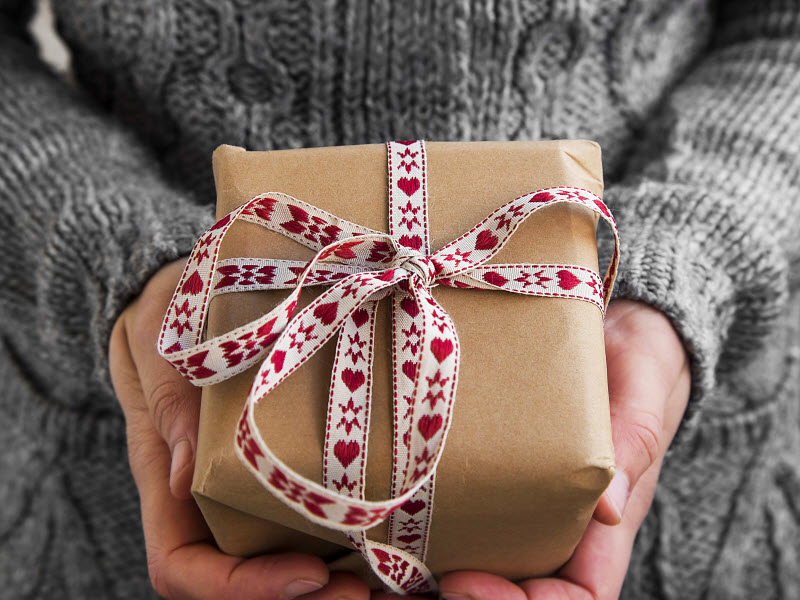 Woman holding a gift with a ribbon