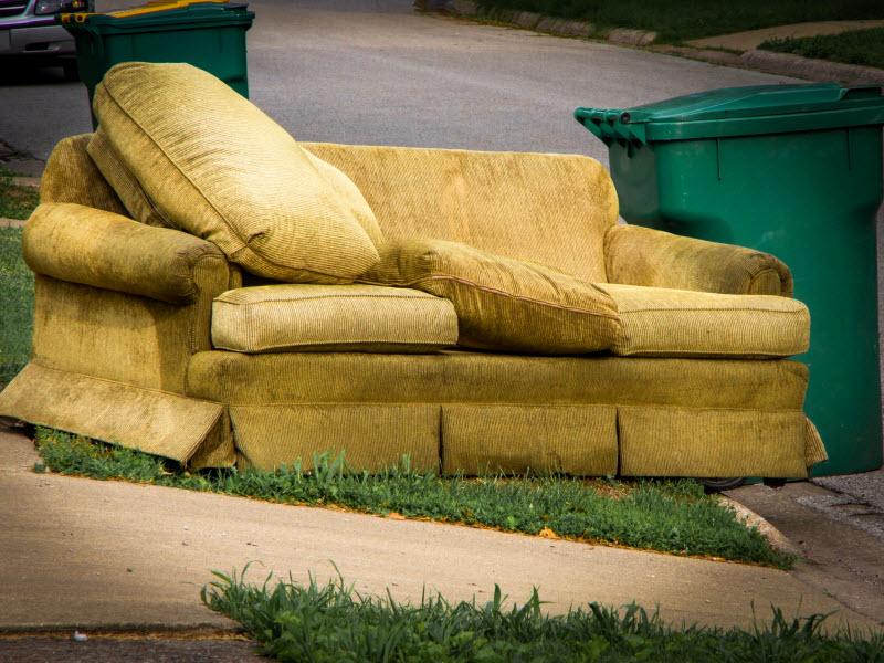 Old sofa placed in the frontyard beside a garbage bin