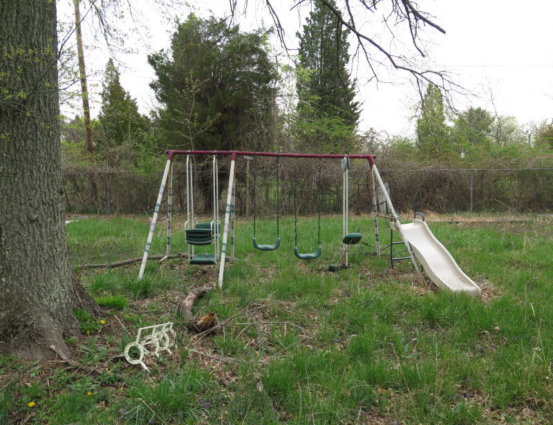 Old swing with slide on an abandoned property
